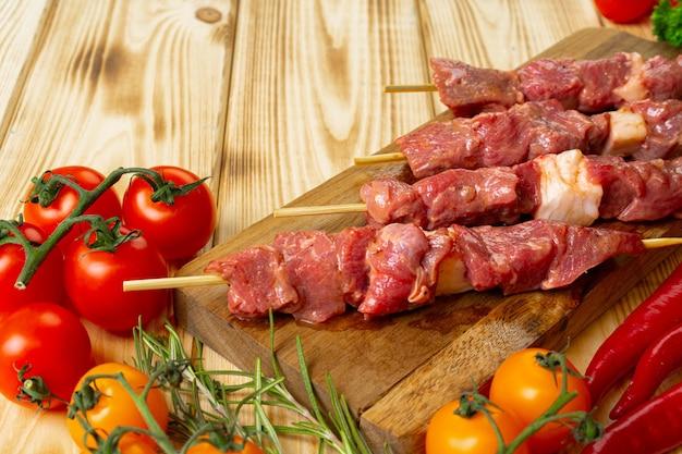 野菜と木製の背景に肉から生ケバブ。