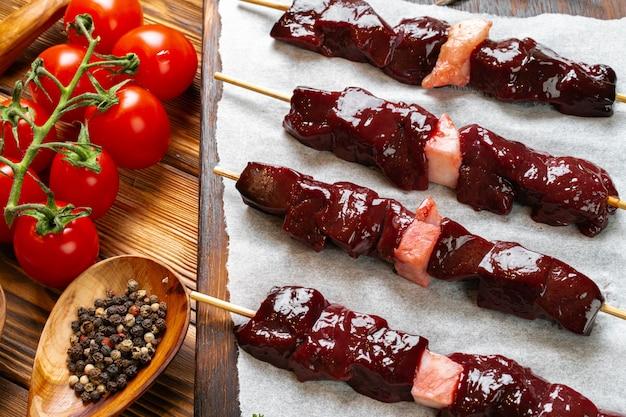 野菜と木製のテーブルの肉から生のケバブ。