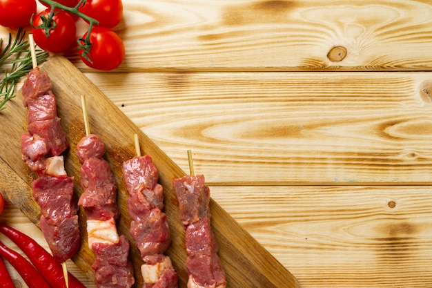 Raw kebab from meat on wood with vegetables.