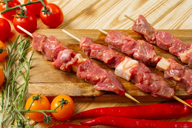 Raw kebab from meat on a wooden table with vegetables.