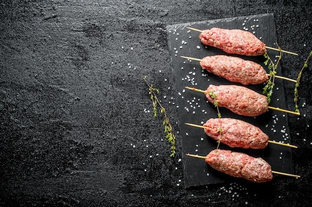 백리향과 소금 조각을 곁들인 간 쇠고기 생 케밥. 검은 소박한 표면에