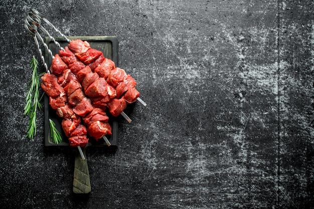 로즈마리와 함께 커팅 보드에 원시 케밥입니다. 검은 소박한 표면에