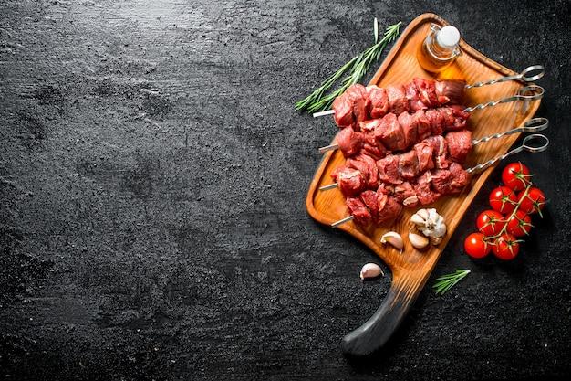 Сырой шашлык на разделочной доске с помидорами, чесноком, розмарином и маслом. на черном деревенском