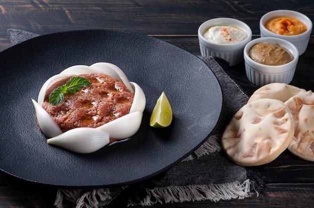 Raw kebab with side dishes, hummus, babaganoush, curd and pita bread. arabic food.