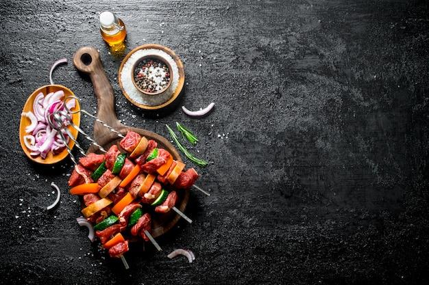 野菜、スパイス、油、黒い木製のテーブルのボウルに玉ねぎを切った生ケバブ