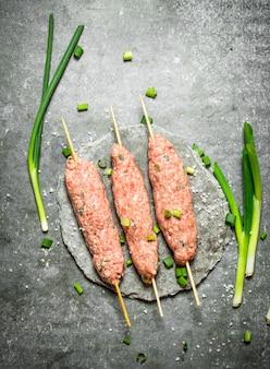 ネギと木製の串焼きの生ケバブ。
