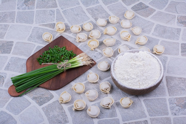 Raw khinkali doughs on the flour with a bunch of green onion.