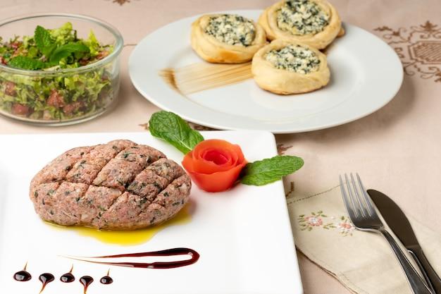白い皿に生のキッベアラビア料理の典型的な食べ物