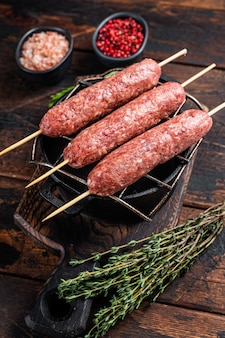 Raw kofta or lula kebabs skewers on a grill with herbs. dark wooden background. top view.