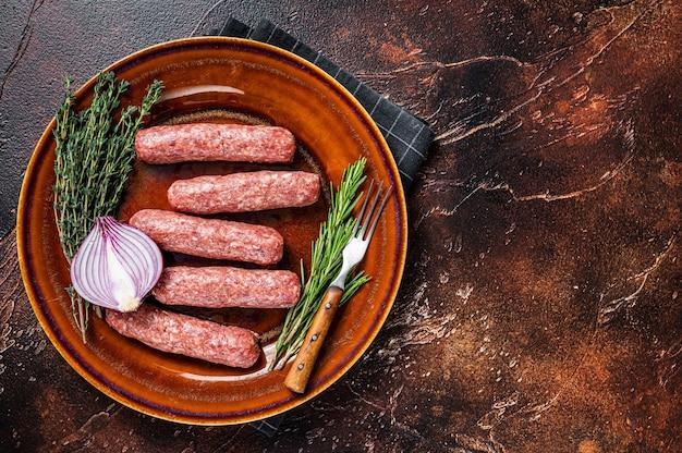 Сырые сосиски кебаб из мяса кофта на тарелке с зеленью. темный фон. вид сверху. скопируйте пространство.