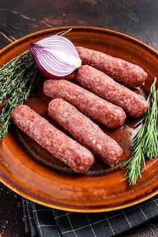 Сырые сосиски кебаб из мяса кофта на тарелке с зеленью. темный фон. вид сверху.