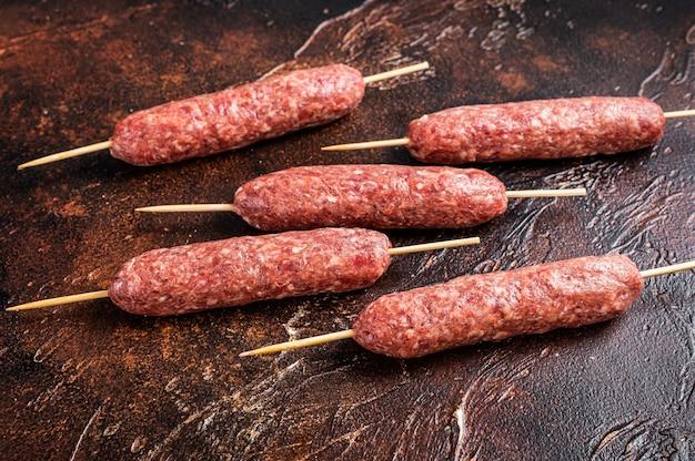 Шашлык из сырого мяса кофта на шпажках. темный фон. вид сверху.