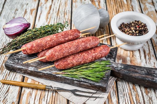 Сырые мясные колбаски кофта или люля-кебаб на шпажках с зеленью. темный деревянный фон. вид сверху.
