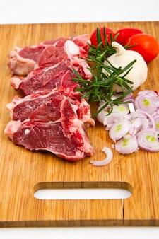 Raw lamb chops and fresh vegetables
