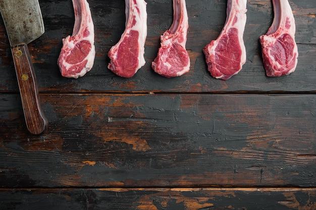 Сырые отбивные из баранины или нарезки из баранины и старый нож мясника на старом темном деревянном столе