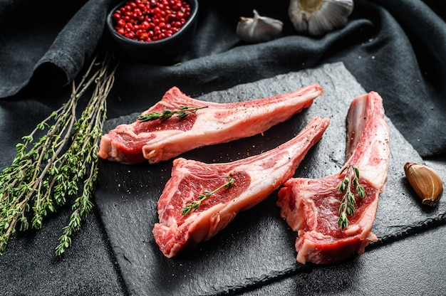 Raw lamb chops, rack of lamb with rosemary and spices.