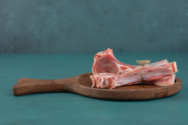 Raw lamb chops on wooden board.