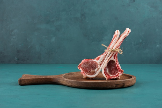 Raw lamb chops on wooden board.