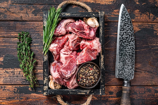 Raw lamb or goat meat diced for stew with bone. dark wooden