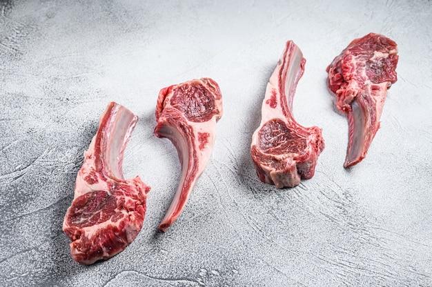 Сырые отбивные из мяса ягненка на столе мясника. белый фон. вид сверху.