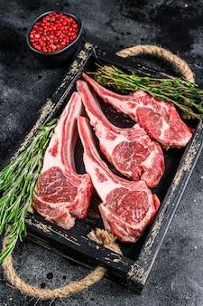 Сырое мясо ягненка отбивает стейки в деревянном подносе. черный фон. вид сверху.