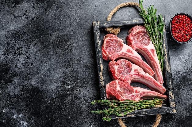 Сырое мясо ягненка отбивает стейки в деревянном подносе.