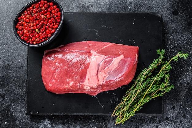 石板に生のラム肉のレッグステーキ