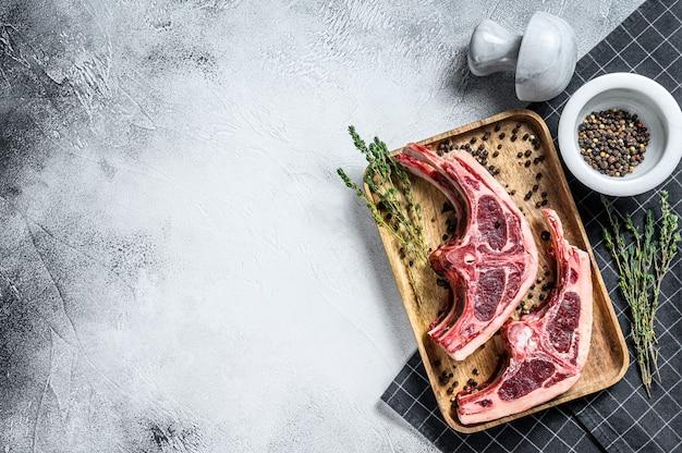 Сырое мясо ягненка на ребрышках с розмарином и специями. серый фон вид сверху. копировать пространство