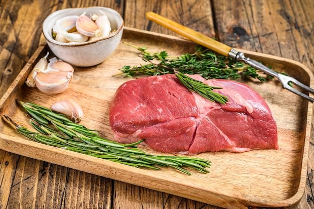 ハーブと木製トレイの生ラム肉ステーキ