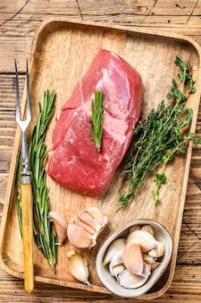 Стейк из сырого мяса ягненка на деревянном подносе с зеленью