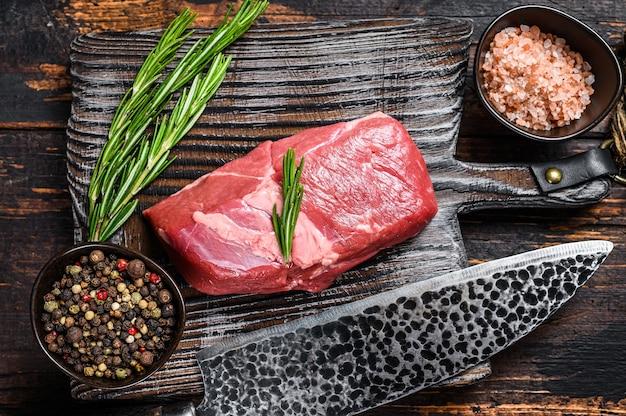 ハーブと木製のまな板の上に生の子羊の肉ステーキ