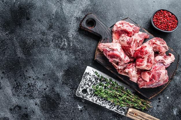 Сырое тушеное мясо ягненка с косточкой на деревянной доске мясника и тесаке. чернить