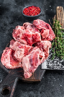 Raw lamb meat stew cuts with bone on wooden butcher board and cleaver. black