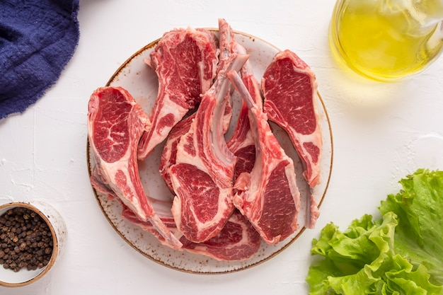 Сырое мясо ягненка со специями на тарелке. вид сверху