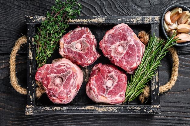 칼으로 정육점 테이블에 원시 양고기 목 고기. 검은 나무 배경. 평면도.