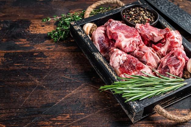 Сырое мясо ягненка или козлятины, нарезанное кубиками для тушения с косточкой. темное дерево