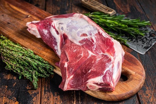 Сырое мясо ягненка или козла на кости на деревянной разделочной доске мясника с тесаком. темный деревянный фон. вид сверху.
