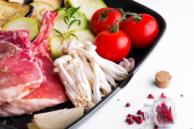 白い石のグリル鍋で新鮮な野菜とマリネした生の子羊のリブ