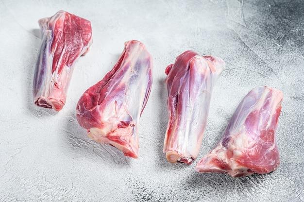 生の子羊のすね肉を石のテーブルに載せます。白いテーブル。上面図。