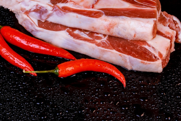 Raw lamb shanks with pepper on stone tray on table, selective focus