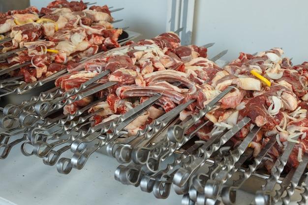 生の子羊の串焼きをグリルする前に串に刺します