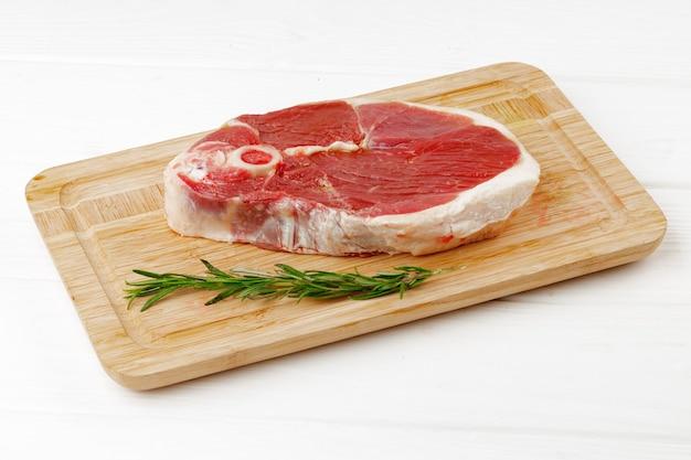 흰색 나무 테이블에 보드에 원시 양고기 스테이크