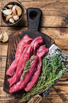 고기 식칼과 정육점 보드에 원시 양고기 안심 등심 고기. 나무 배경입니다. 평면도.