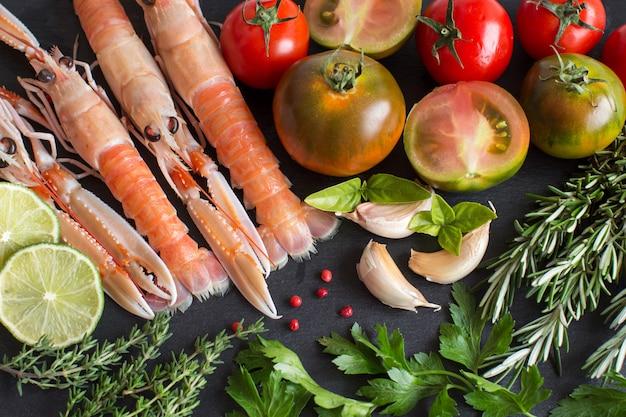 野菜とハーブの生手長エビは黒いテーブルにクローズアップ