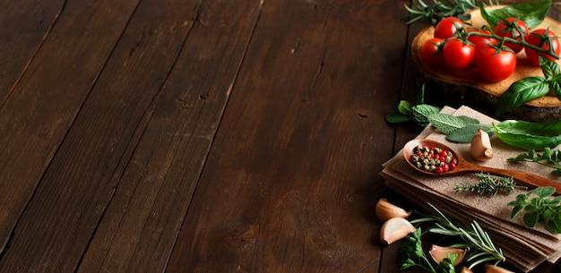 木製のテーブルに生のラザニアパスタ、野菜、ハーブ