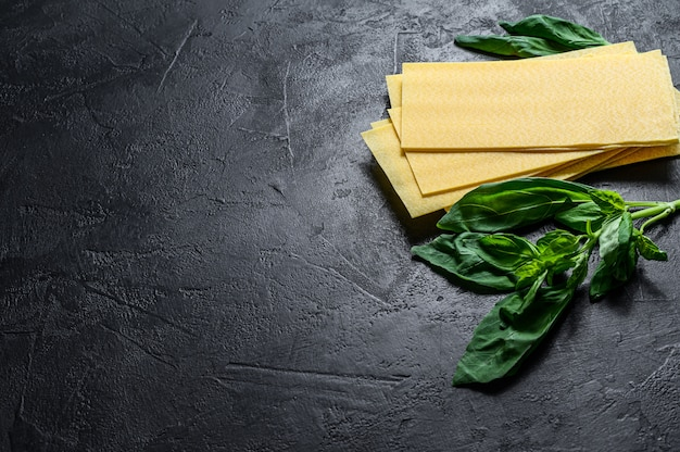 Raw lasagna sheets and basil leaves. black background. top view. space for text