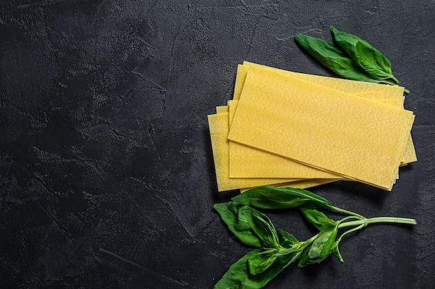 Raw lasagna sheets and basil leaves.