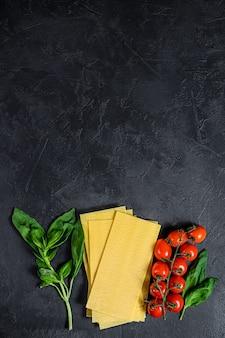 Raw lasagna sheets. ingredients basil, cherry tomatoes.