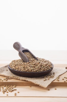 Raw lentils on wooden plate and scoop