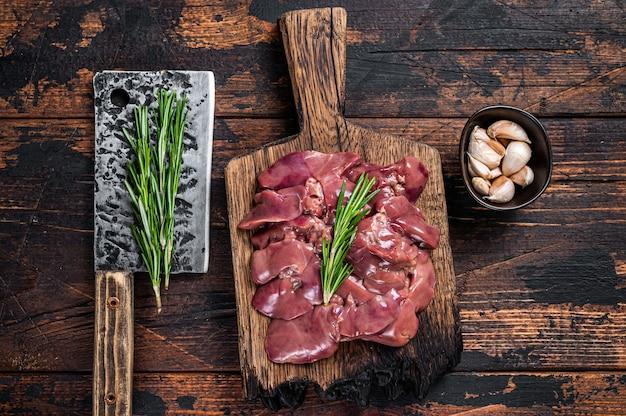 生のレバーチキンは、肉屋の包丁で木製のまな板の上で肉を内臓します。暗い木製のテーブル。上面図。